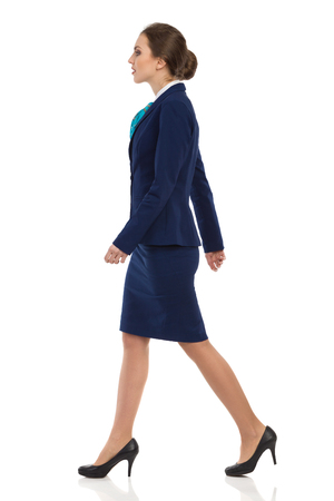 Young woman in blue suit, skirt and black high heels walking. Side view. Full length studio shot isolated on white.