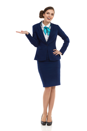 Smiling young businesswoman in blue formalwear and high heels is standing with hand raised and looking at camera. Front view. Full length studio shot isolated on white.