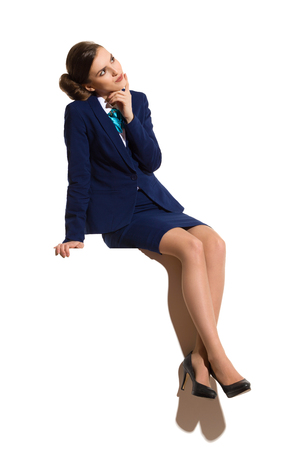 Young woman in blue formal businesswear and black high heels, sitting on a top with legs crossed, thinking and looking up. Full length studio shot. Stock Photo