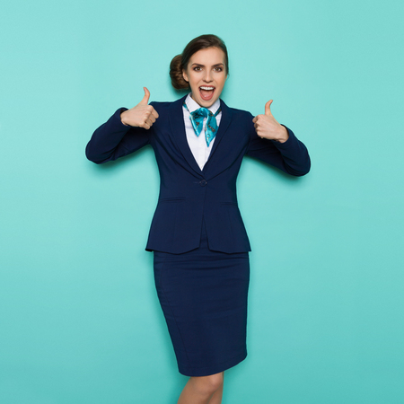 Excited stewardess in blue formal wear, standing with arms raised, showing thumbs up, shouting and looking at camera. Three quarter length studio shot on turquoise background.