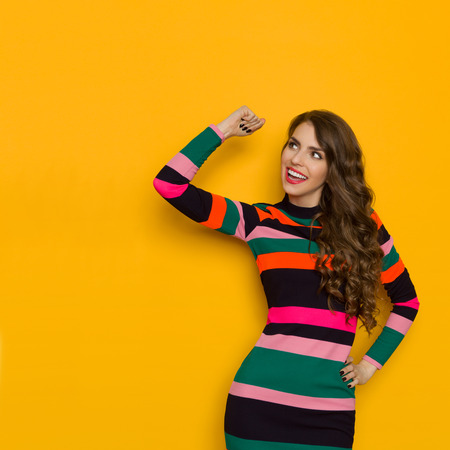 Happy beautiful young woman in colorful vibrant striped dress with long sleeves is holding arm raised, smiling and looking away. Three quarter length studio shot on yellow background. Stock Photo
