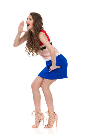 Beautiful young woman in multicolored mini dress and high heels is standing with hands raised, shouting and looking away. Side view. Full length studio shot isolated on white.