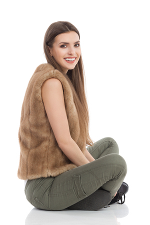 khaki: Beautiful young woman in brown fur waistcoat and khaki pants sitting on floor with legs crossed, smiling and looking at camera. Side view. Full length studio shot isolated on white.