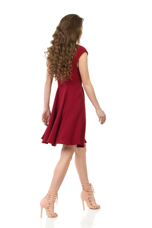 Long haired young woman in elegant maroon dress and high heels is walking and looking at camera. Front view. Full length studio shot on isolated on white. Stock Photo