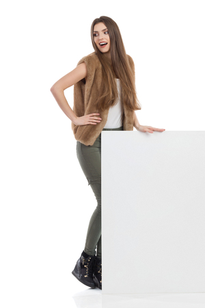 Cheerful young woman in brown fur waistcoat, khaki pants and black boots is standing behind blank placard and looking away over the shoulder. Full length studio shot isolated on white.