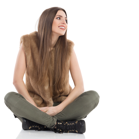 Beautiful young woman in brown fur waistcoat and khaki pants sitting on floor with legs crossed, smiling and looking away. Full length studio shot isolated on white.
