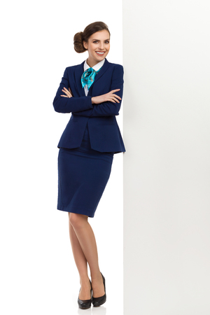 Young stewardess in blue formalwear and high heels is standing close to white wall, holding arms crossed and smiling. Front view. Full length studio shot isolated on white.