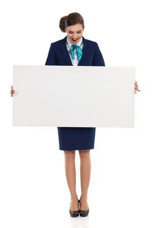 Happy young woman in blue formalwear and high heels is holding blank placard, looking on it and reading. Front view. Full length studio shot isolated on white.
