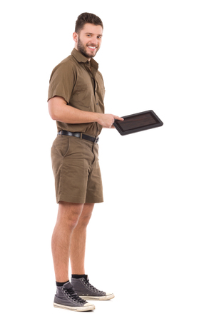 Smiling delivery man in khaki uniform is standing, holding digital tablet and pointing on it. Full length studio shot isolated on white. Stock Photo