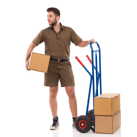 Male courier is standing close to push cart, holding package under his arm and looking away. Full length studio shot isolated on white.
