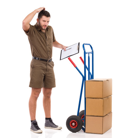 Confused delivery man is standing close to a moving cart, holding clipboard and scratching his head. Full length studio shot isolated on white. Stock Photo