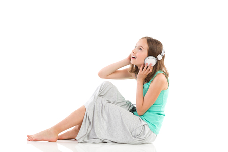 Ecstatic young girl with headphones is sitting on the floor and listening to the music. Full length studio shot isolated on white.