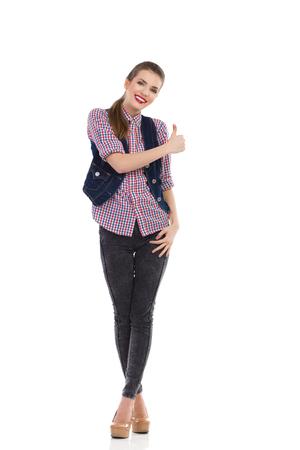 Beautiful smiling girl showing thumb up. Full length studio shot isolated on white.