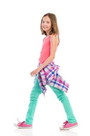 Cheerful teen girl walking, side view. Full length studio shot isolated on white.