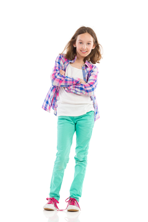 Young girl in lumberjack shirt and green trousers posingp. Full length studio shot isolated on white.