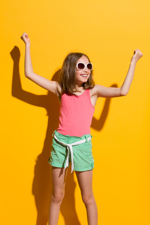 Happy teen girl with arms raised. Three quarter length studio shot on yellow background.