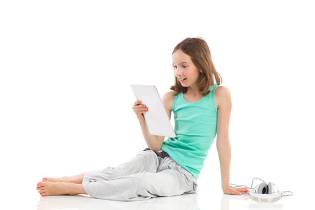 Surprised girl sitting on the floor and reading something at a digital tablet. Full length studio shot isolated on white. Stock Photo