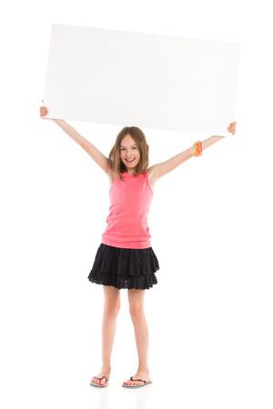 Cute little girl holding blank banner over her head and smiling. Full length studio shot isolated on white.