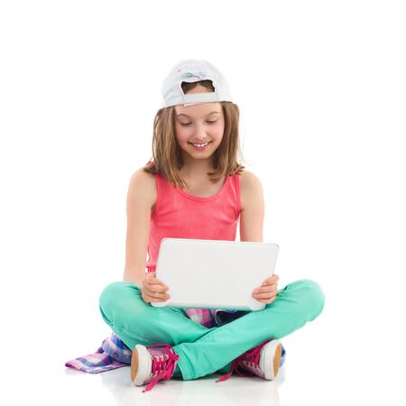 Smiling girl in baseball cap sitting on the floor with legs crossed and holding digital tablet. Full length studio shot isolated on white.