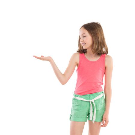 손 팜을 잡고 웃는 어린 소녀를 열고 제품을 제시합니다. 3 분기 길이 스튜디오에 격리 된 흰색을 쐈 어.