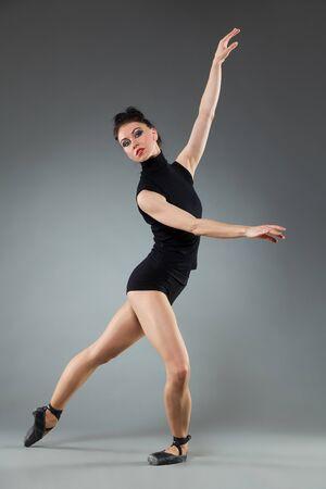legs apart: Female ballet dancer is posing in legs apart and arms raised. Full length studio shot on gray background. Stock Photo