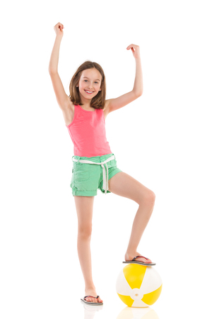Cheering girl in pink shirt and green shorts posing with a beach ball under her foot. Full length studio shot isolated on white.