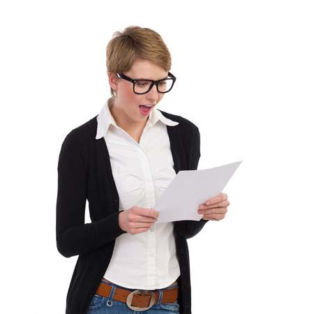 raised eyebrow: Young woman reading documents and looking surprised. Waist up length studio shot isolated on white.