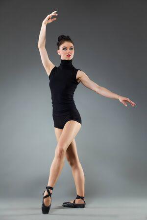 Female ballet dancer is posing with arms raised. Full length studio shot on gray background. Stock Photo