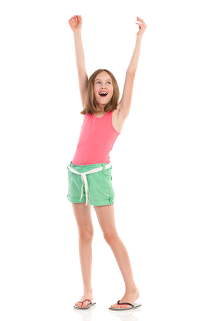 Shouting girl with arms raised looking away. Full length studio shot isolated on white.