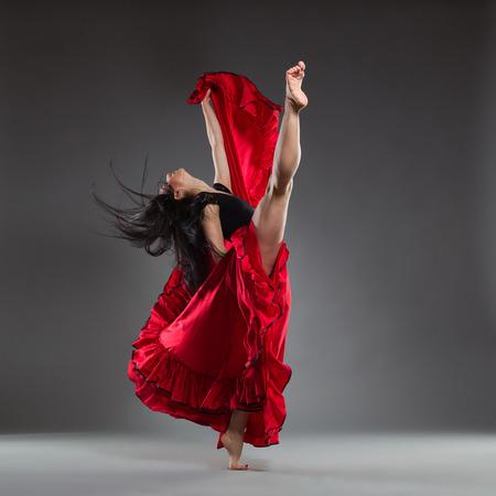 Ballet dancer in red dress. Full length studio shot on gray background.