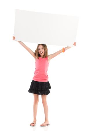one sheet: Cute little girl holding blank banner over her head and shouting. Full length studio shot isolated on white.