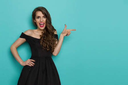 Beautiful young woman in elegant black cocktail dress is shouting, looking at camera and pointing. Three quarter length studio shot on turquoise background. Stock Photo