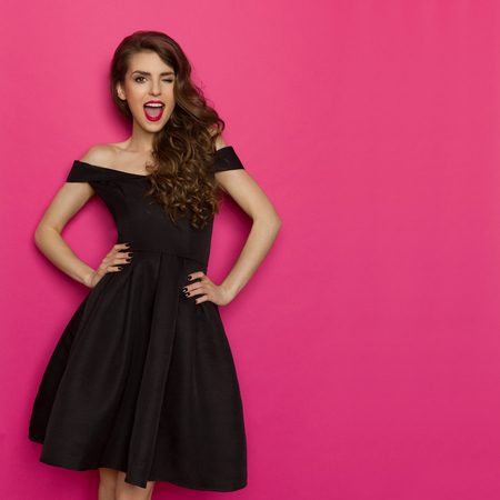 Beautiful young woman in elegant black cocktail dress is holding hands on hip, winking, laughing and looking at camera. Three quarter length studio shot on pink background. Stockfoto