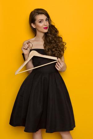De mooie jonge vrouw in elegante zwarte cocktailkleding houdt houten hanger en bekijkt camera. Drie kwart lengtestudio die op gele achtergrond is ontsproten.