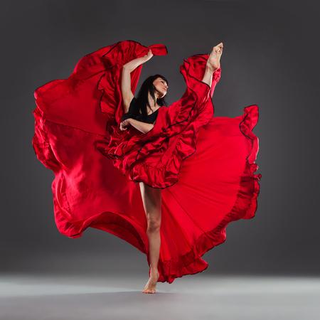 Female in red dress is dancing on one leg. Full length studio shot on gray background.