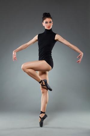 Female ballet dancer is posing on one leg. Full length studio shot on gray background. Stock Photo