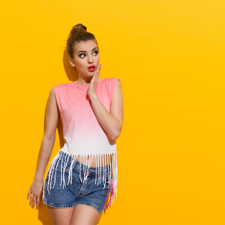 Surprised girl is leaning on the wall and looking away. Three quarter length studio shot on yellow background.