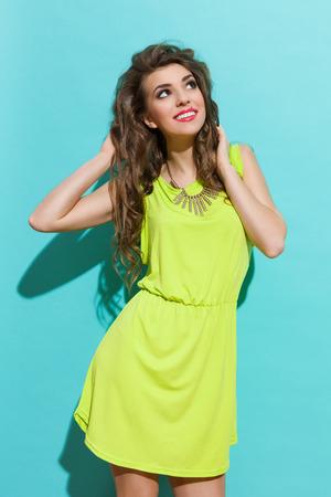 햇빛을 즐기는 라임 그린 드레스에서 아름 다운 여자. 3 분기 길이 스튜디오 청록색 배경에 쐈 어. 스톡 콘텐츠