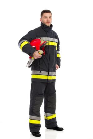 Brandweerman poseren en houdt rode helm onder zijn arm. Full length studio shot geïsoleerd op wit.