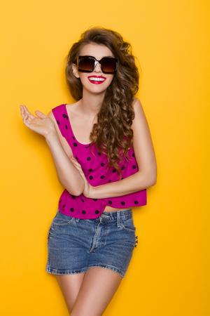 웃는 젊은 여자 선글라스 포즈입니다. 3 분기 길이 스튜디오 노란색 배경에 쐈 어.