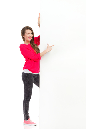 one sheet: Smiling young woman is standing behind big placard and pointing. Full length studio shot isolated on white. Stock Photo
