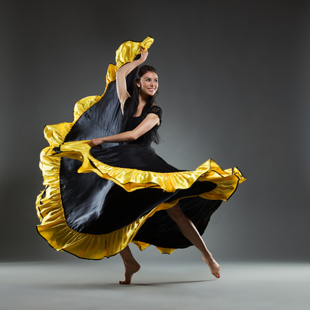 Smiling woman in black and yellow dress is dancing. Full length studio shot on gray background. Stock Photo