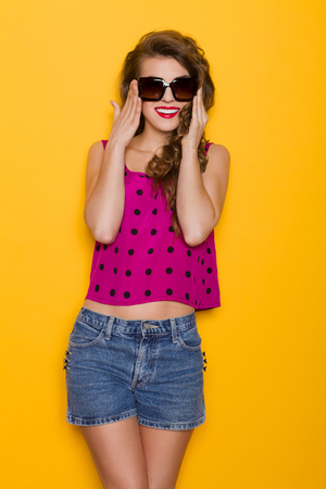 Beautiful young woman is posing in sunglasses. Three quarter length studio shot on yellow background.