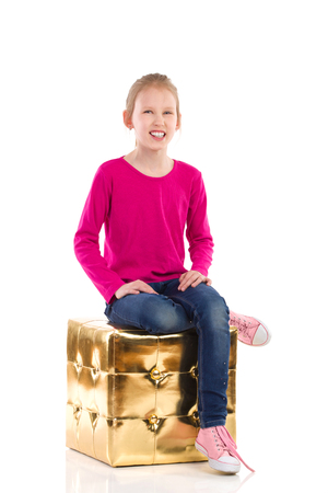 hassock: Smiling girl is sitting on a gold pouffe. Full length studio shot isolated on white.
