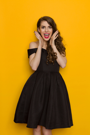 thrilled: Amused beautiful young woman in elegant black cocktail dress is shouting and looking at camera. Three quarter length studio shot on yellow background. Stock Photo