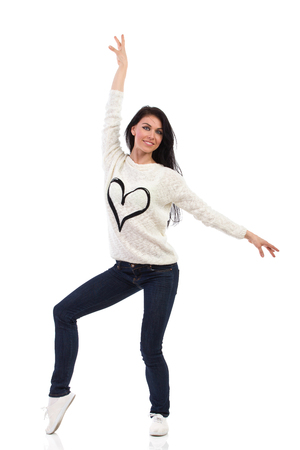 Smiling female dancer posing with heart at the jersey. Full length studio shot isolated on white.