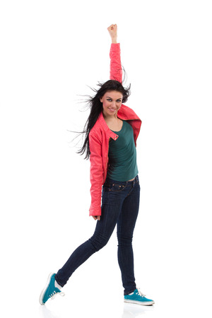 Smiling female dancer is posing and punching the air. Full length studio shot isolated on white.