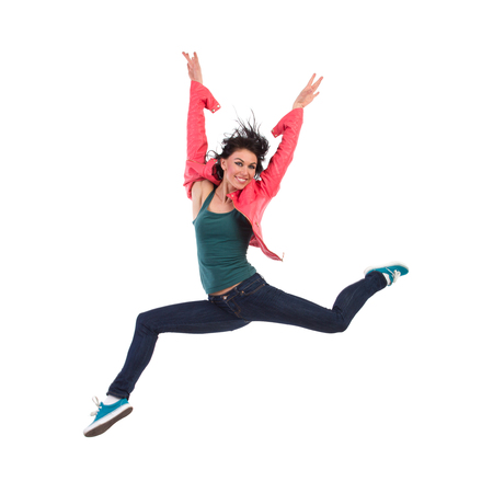 legs apart: Smiling woman jumping with arm raised. Full length studio shot isolated on white.