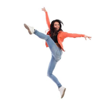 Smiling woman is jumping with arms outstretched. Full length studio shot isolated on white. Stock Photo