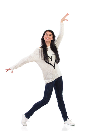 Smiling woman posing with arms outstretched. Full length studio shot isolated on white.